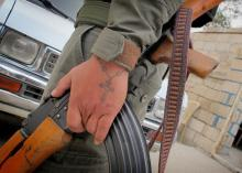 Syrian Christian soldier with gun and crucifix tattoo